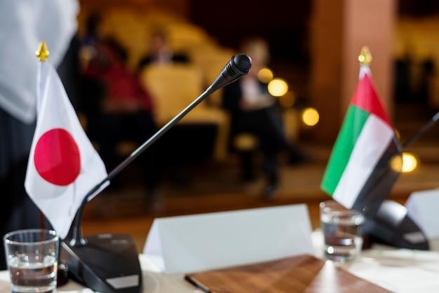 国際会議でマイクを使ってテーブルの上の日本と首長国連邦旗 Premium写真