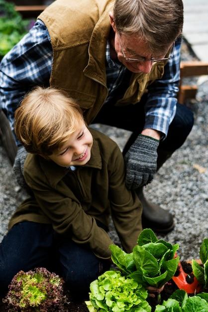 裏庭の庭から野菜を選ぶ家族 Premium写真