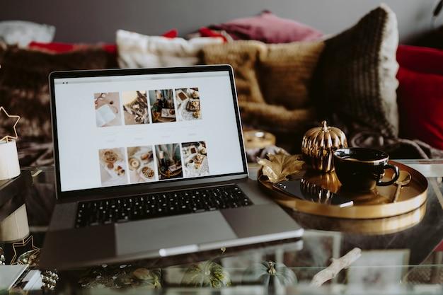 写真フィードを示すガラステーブルの上のノートパソコン Premium写真