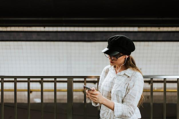 電車を待っている間音楽を聴いている女の子 無料写真