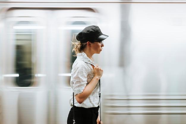 地下鉄のプラットフォームで電車を待っている思いやりのある女性 無料写真