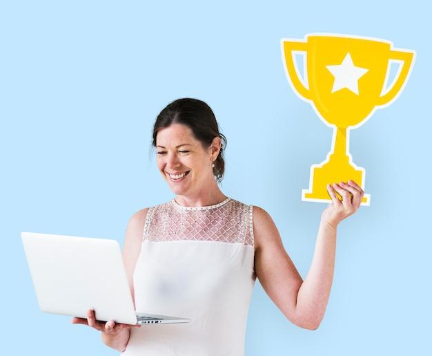 女性のトロフィーアイコンを押しながらラップトップを使用して 無料写真