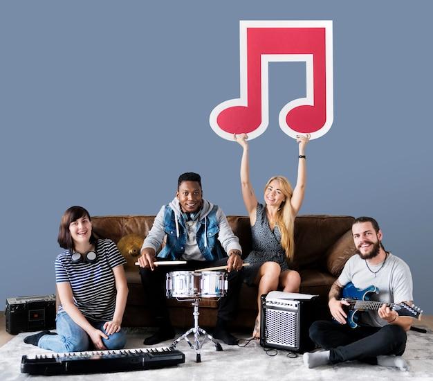 音符のアイコンを保持しているミュージシャンのバンド 無料写真