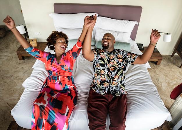 アフリカ系アメリカ人カップル、ベッドでリラックス Premium写真
