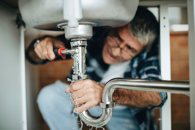 台所の流しを固定する配管工 Premium写真