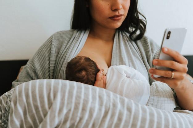 スマートフォンを使用しての母乳育児中の母親 Premium写真