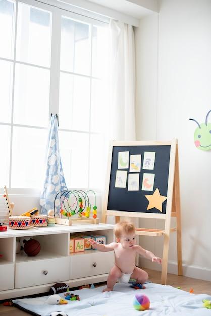 遊戯室でおむつの赤ちゃん Premium写真