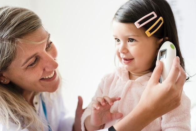 耳鼻咽喉科医、甘い小さな女の子をチェック Premium写真