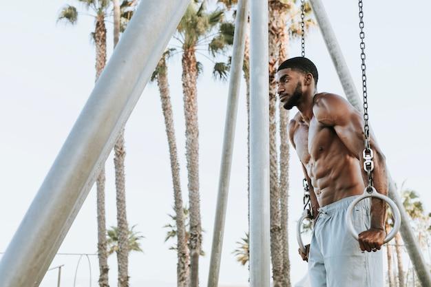 ぴったりの男性、ビーチでのエクササイズ Premium写真