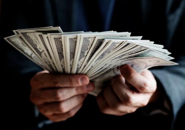 Макрофотография руки, держащей деньги Premium Фотографии