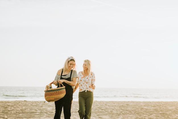 Друзья гуляют по пляжу с корзиной для пикника Бесплатные Фотографии