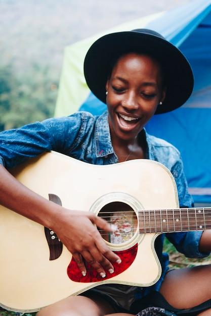 ギターを弾くと屋外レクリエーション一緒に歌うキャンプサイトで若い大人の友人のグループ Premium写真