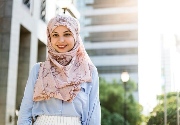 Исламская женщина стоит и улыбается в городе Premium Фотографии