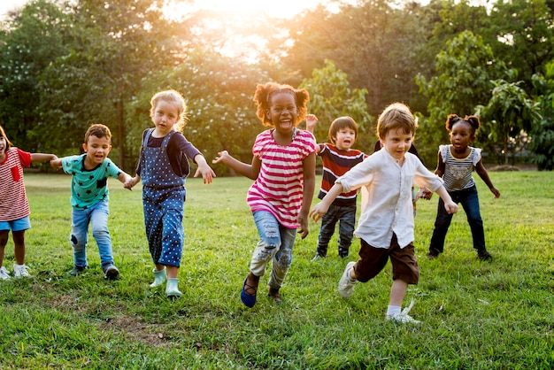 一緒にフィールドで遊ぶ多様な子供たちのグループ Premium写真
