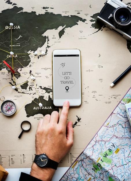 マップの背景の上に携帯電話を持つ手のクローズアップ Premium写真
