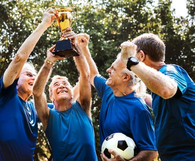 カップを獲得した成熟したフットボール選手のチーム Premium写真