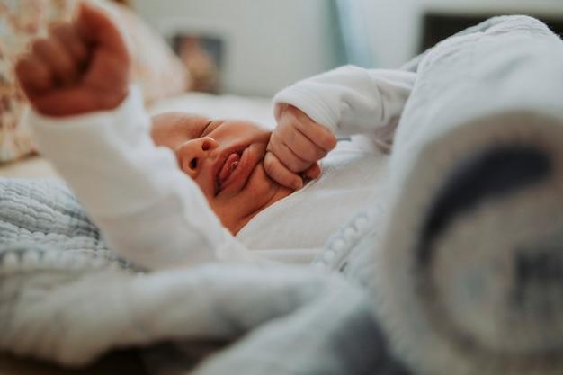 あくびベッドの上の幼児の赤ちゃん Premium写真