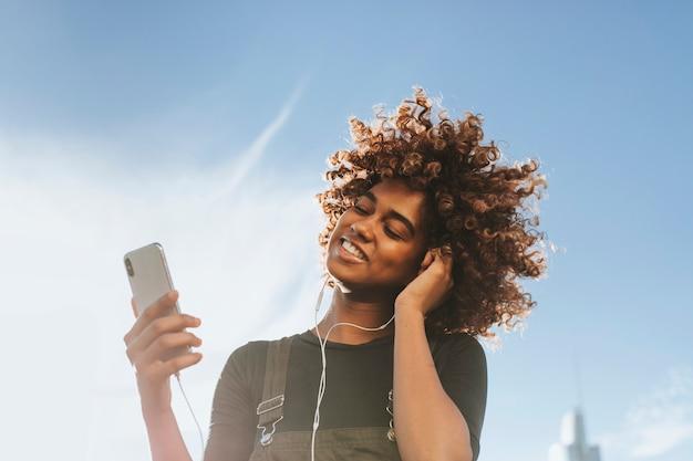 彼女の電話から音楽を聴いている女の子 Premium写真