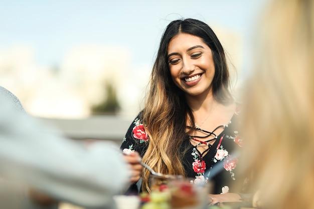 彼女の友達と屋上パーティーを楽しんでいる陽気な女性 Premium写真