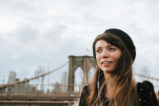 ブルックリン橋、アメリカで音楽を聴く女性 Premium写真