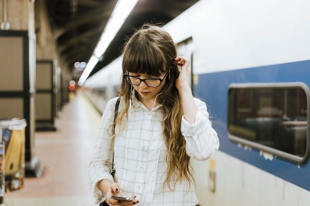 思いやりのある女性が地下鉄の駅で電車を待っている間音楽にリスト Premium写真