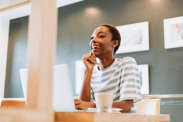 カジュアルな女性がカフェで働く Premium写真