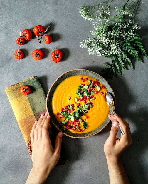 パセリとザクロの種をのせた新鮮なカボチャスープ Premium写真