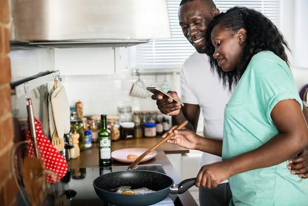台所で揚げ卵を調理するカップル Premium写真