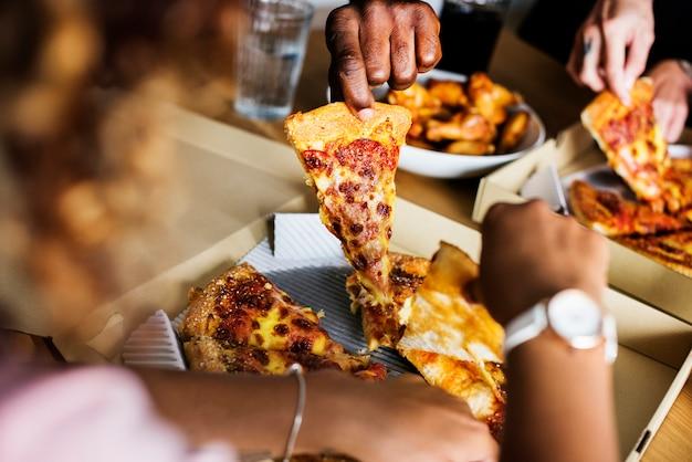 Друзья едят пиццу вместе дома Premium Фотографии