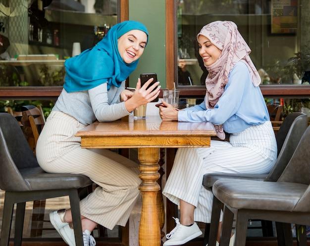 Исламские друзья говорят и смотрят на смартфон Premium Фотографии