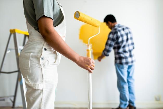 Человек красит стены желтым Premium Фотографии