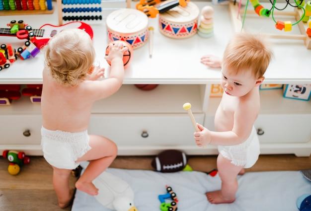 Дети в подгузниках играют вместе Premium Фотографии