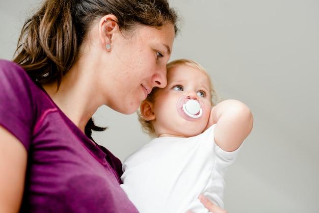 彼女のかわいい赤ちゃんを運ぶお母さん Premium写真