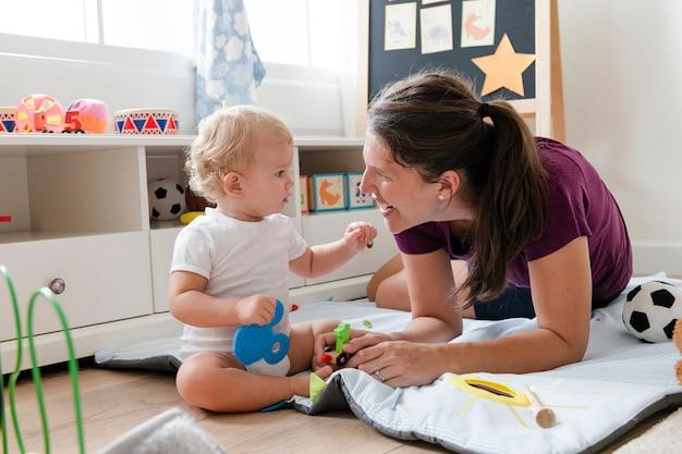 床に彼女の赤ちゃんと遊ぶ母 Premium写真