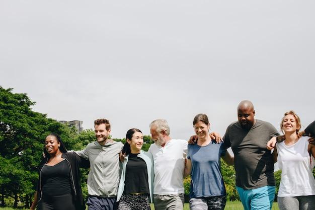 Группа людей, обнимающих друг друга в парке Premium Фотографии