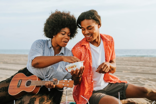 ビーチでピクニックを持っているカップル Premium写真