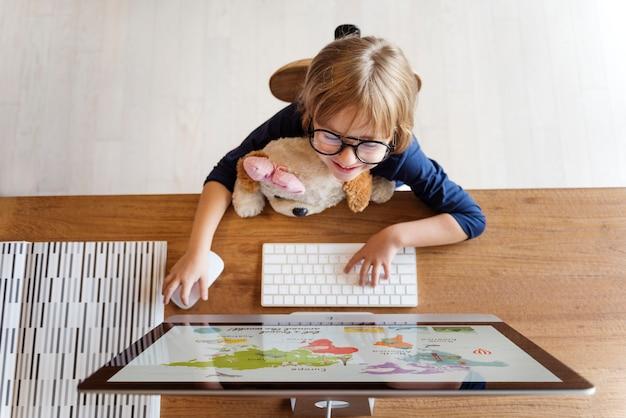 Маленькая девочка с помощью компьютерной концепции Premium Фотографии