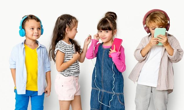 音楽を聴くキュートで愛らしい子供たちの幸せグループ Premium写真
