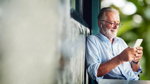 スマートフォンを持つ老人 Premium写真