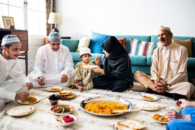 床で夕食を食べているイスラム教徒の家族 Premium写真