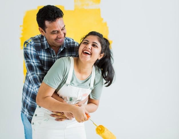 Веселая пара красит стены в желтый цвет Premium Фотографии