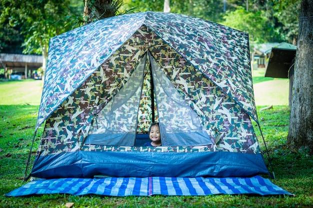 キャンプをしながらテントに座っている小さな女の子。 Premium写真