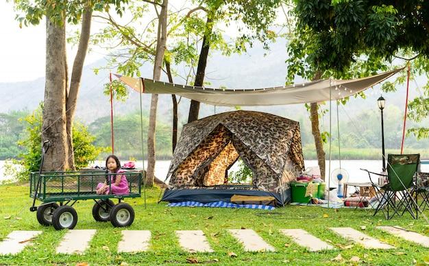 キャンプに行きながらワゴンに座っている小さな女の子。 Premium写真