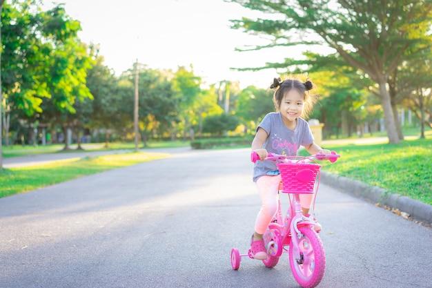 公園、子供のスポーツ、アクティブなライフスタイルで運動する自転車に乗ってかわいいアジアの女の子 Premium写真
