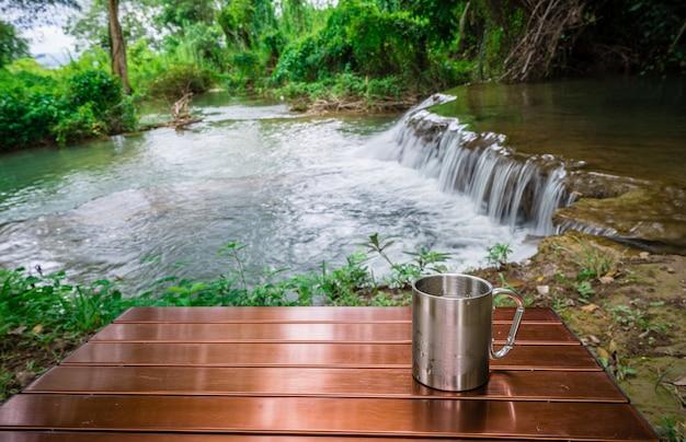 休日のキャンプ間の滝の前のテーブルに冷たい飲み物のカップ Premium写真