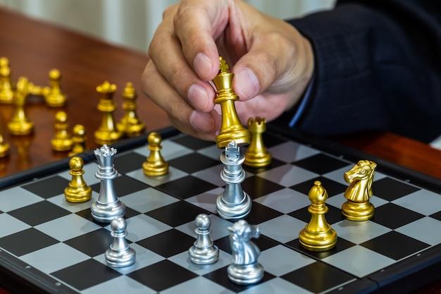 Игра в шахматы на шахматной доске за предпосылкой бизнесмена. бизнес-концепция для представления финансовой информации и анализа маркетинговой стратегии. Premium Фотографии