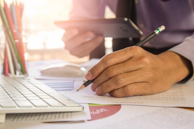ビジネスマンや会計士のビジネスデータの概念を計算するための電卓に取り組んで Premium写真