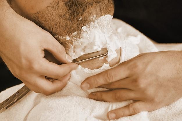 Профессиональное бритье. съемка крупного плана парикмахера брея его клиента с бритвой Premium Фотографии