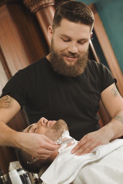 Наслаждаясь современной парикмахерской. вертикальный портрет человека побрился в местной парикмахерской Premium Фотографии