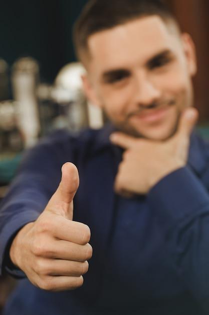 Он любит свою бороду. выборочный фокус на руке клиента парикмахерской показывает палец вверх жест Premium Фотографии
